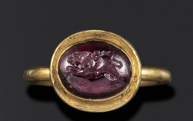 A Hellenistic domed garnet intaglio of Eros riding a lion, c2nd-1st century BC, in a late Roman gold ring, c4th-5th century AD, intaglio 1.1cm high, ring size L