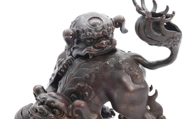 A Japanese patinated bronze center in shape of two Shishi at play. Signed Daiho. Meiji 1868–1912. H. 14 cm.