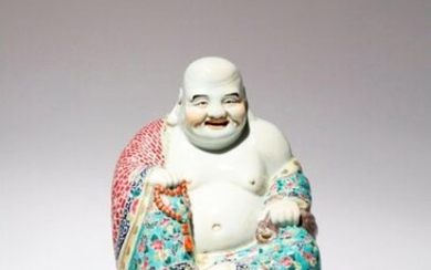 A LARGE CHINESE FAMILLE ROSE FIGURE OF BUDAI HE SHANG EARLY 20TH CENTURY He sits in a relaxed pose with a cheerful expression on his face, dressed in bright turquoise and cherry-coloured robes decorated with blossoms and abstract designs, he holds a...