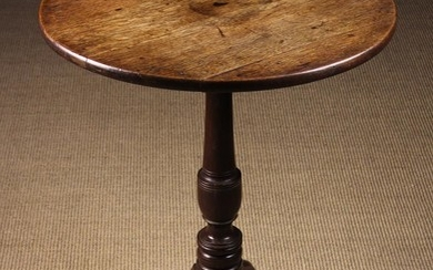 A Small Oak Tilt-top Tripod Table. The round planked top on a turned urn-knopped centre column and o