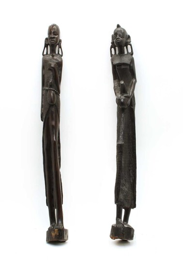 A pair of African carved ebony figures of water carriers
