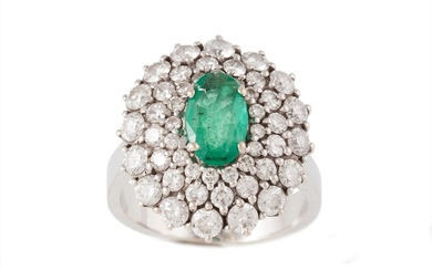AN EMERALD AND DIAMOND OVAL CLUSTER RING, with emerald of ap...