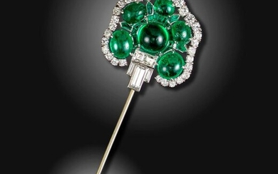 An emerald and diamond-set jabot pin, of stylised palmette form, set with six cabochon emeralds within a surround of calibre-cut emeralds and baguette-shaped diamonds, with an undulating outer border of round brilliant-cut diamonds, the smaller...