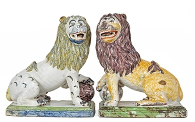 "Pair of ""Seated Lions, one paw on a globe"" in polychrome earthenware"