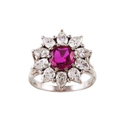 A RUBY AND DIAMOND CLUSTER RING, the cushion cut ruby to a m...