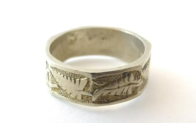 A white metal ring with foliate decoration. Marked '15'