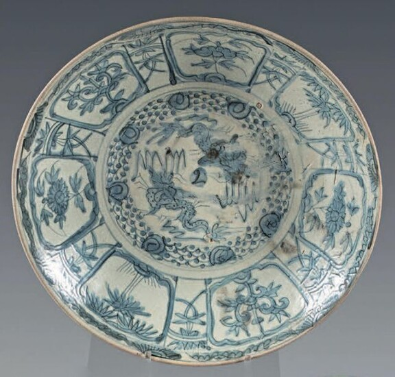 Chinese glazed stoneware dish (Swatow). 17th century. With blue-white decoration, in the center of two dragons in a medallion, the wing and the fall of flowers and trees in interspersed reserves, braid on the edge, floral motifs on the reverse, small...