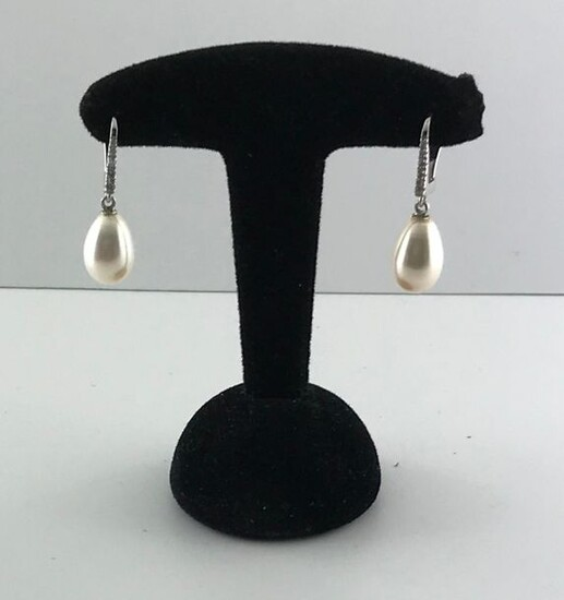 Pair of 750°/°°° white gold sleepers set with a line of diamonds holding a pear-shaped freshwater cultured pearl in pendants, Gross weight: 4,02g