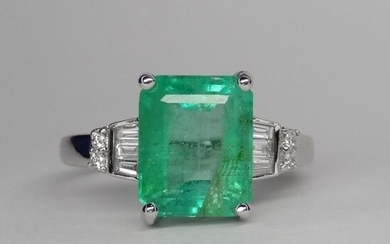 Ring in white gold, 750 MM, set with a 2.85 carat cut-sided transparent emerald set with baguette - trapezium cut diamonds set with four brilliants, size 15 / 10 mm, cut: 52, weight: 4.1gr. rough.