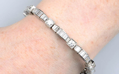 A brilliant and baguette-cut diamond line bangle.
