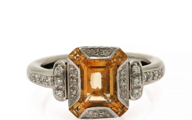 A citrine and diamond ring set with an emerald-cut citrine encircled by four square-cut citrines and numerous brilliant-cut diamonds, mounted in 14k white gold.