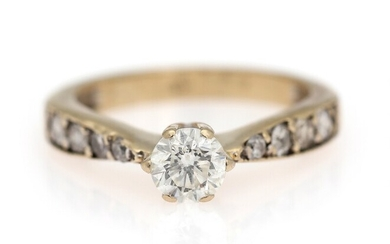 SOLD. A diamond solitaire ring set with a diamond weighing app. 0.70 ct. flanked by...