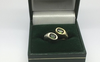 A modern design ring set with two green stones and small dia...