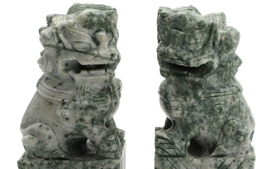 A pair of Chinese carved soapstone figurines of guardian lions. 20th century. H. 17 cm....