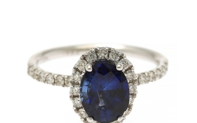A sapphire and diamond ring set with an oval-cut sapphire and numerous brilliant-cut diamonds, mounted in 14k white gold. Size 55.