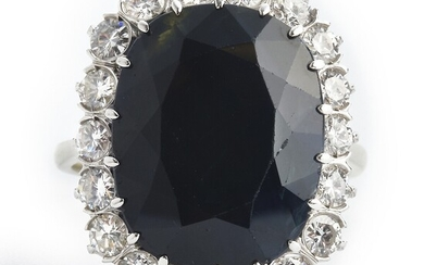 A sapphire and diamond ring set with an oval-cut sapphire weighing app. 15.00 ct. encircled by numerous brilliant-cut diamonds, mounted in 18k white gold.