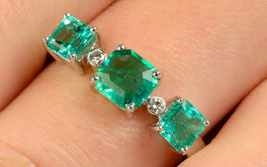 An emerald three-stone ring, with brilliant-cut diamond spacers.
