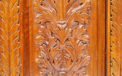 Henri II style base cabinet in carved and molded walnut wood, decorated with scrolls, birds and mask; opening to a swinging door.