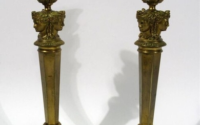 Pair of bronze candleholders with a golden patina and decorated with a three-faced caryatid, the shafts in the form of a sheath. Empire period - Ht : 29,5 cm each - Drilled for electricity (three shocks on the base of one of the candle-holders)