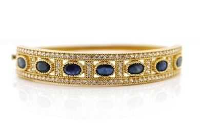 Sapphire and 14ct yellow gold hinged bangle with a cubic zir...