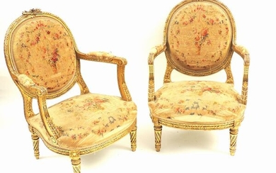 A pair of gilted and curved armchairs