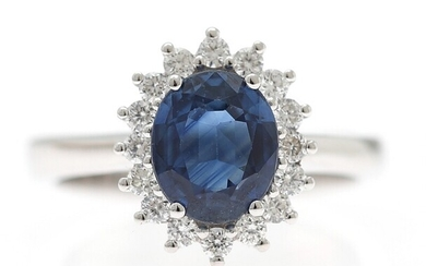A sapphire and diamond ring set with an oval-cut sapphire encircled by numerous brilliant-cut diamonds,...