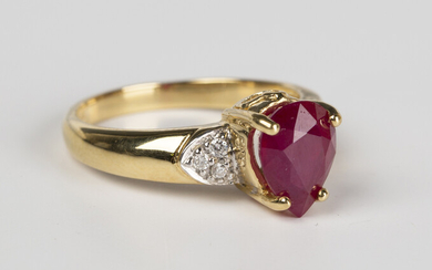An 18ct gold, ruby and diamond ring, claw set with the pear shaped ruby in a raised design between c