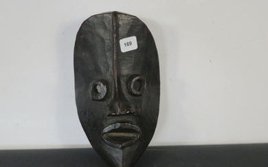 FACIAL MASK. Hard wood, beautiful shiny black patina. Round projecting eyes, lips spread apart, the nasal appendage is extended by a raised line to the top of the mask. Ivory Coast, Dan High 21 cm