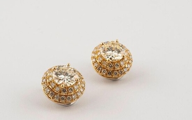 Pair of earrings in two-tone 750°/00 gold, each set with a large diamond (about 3.22 cts) in a double entourage of round brilliant diamonds. Diamond characteristics: in the centre NZVVS, for the HIVVS entourage. Clip system with the possibility of...