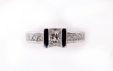 RING in 18K white gold holding twenty-five brilliant-cut diamonds, of which the center diamond is approximately 0.30 carat princess cut. Gross weight: 3.9 gr. TDD: 51. Estimated diamond weight: 0.45 carat. A white gold and diamond ring.