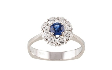 A DIAMOND AND SAPPHIRE CLUSTER RING, the circular sapphire t...