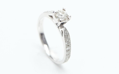 A DIAMOND DRESS RING IN 18CT WHITE GOLD, CENTRALLY SET WITH A ROUND BRILLIANT CUT DIAMOND ESTIMATED 0.23CT, WITH FURTHER DIAMOND DETA..