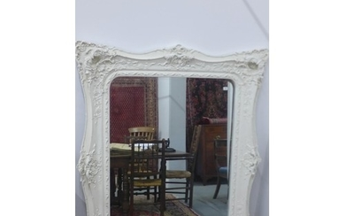A large white ornamental framed mirror with bevelled glass p...