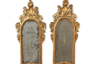 A pair of carved Italian Régence giltwood mirrors. Mirror glasses with etched figural motifs. Ca. 1730. H. 73 cm. W. 28 cm. (2).