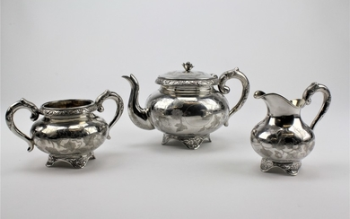 A three piece silver Chinese tea set with floral engraved 10...