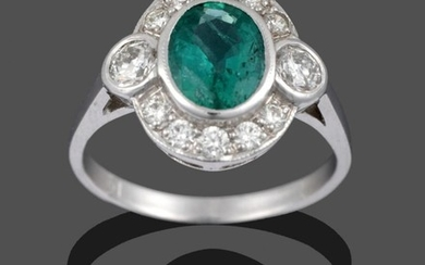 An Emerald and Diamond Ring, the oval cut emerald within...