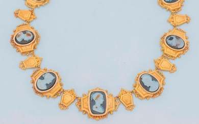 Necklace in 18 karat yellow gold (750 thousandths) composed of articulated links, chiselled and bordered with scrolls, set with seven cameos on brown onyx bicolor or tricolor, depicting profiles of women in antique style. One cameo engraved on the back...