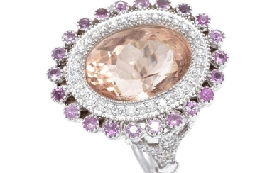 A MORGANITE SAPPHIRE AND DIAMOND COCKTAIL RING; centring a millegrain set oval morganite of approx. 7.00ct within a surround of 34 r...