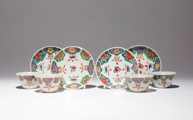 A SET OF FOUR CHINESE FAMILLE ROSE TEA BOWLS AND SAUCERS QIANLONG 1736-95 Each brightly painted in enamels with eight alternating panels enclosing flowers on pink and yellow grounds, the ruyi-head shaped panels suspending beribboned precious objects...