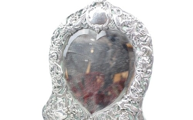 A Silver Heart shaped dressing table mirror embossed and pie...
