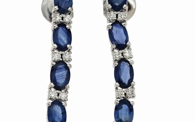 NOT SOLD. A pair of ear pendants each set with five oval-cut sapphires flanked by...