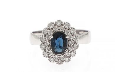 A ring set with a sapphire weighing app. 0.76 ct. encircled by numerous diamonds weighing a total of app. 0.42 ct., mounted in 18k white gold. Size 56.