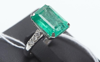 AN EMERALD AND DIAMOND RING IN 18CT WHITE GOLD FEATURING AN EMERALD CUT EMERALD OF 8.62CTS, TO DIAMOND SET SHOULDERS TOTALLING 0.26C...