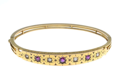 An early 20th century 9ct gold circular-shape ruby and diamond hinged bangle.