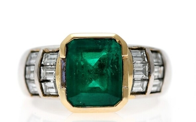 An emerald and diamond ring set with an emerald weighing app. 2.46 ct. flanked by...
