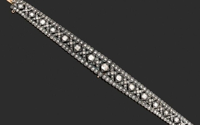 Articulated BRACELET in 750-thousandths gold and 925-thousandths silver, decorated with falling flower motifs adorned with rose-cut and old-cut diamonds, some of them larger, between two lines of diamonds also cut in rose. French work of the 19th...