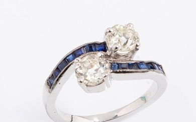 """Ring """"Toi et Moi"""" in 18k (750 thousandths) white gold set with two 0.60 ct diamonds. (VS, J) and 0.66 ct. (SI1, K) paved with square sapphires on the shoulders."""