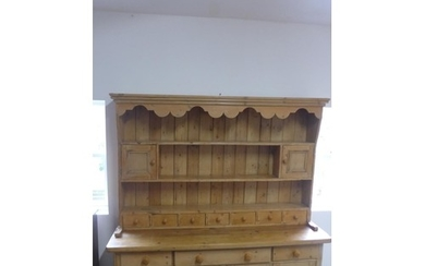 A 19th century and later stripped pine dresser with an open ...