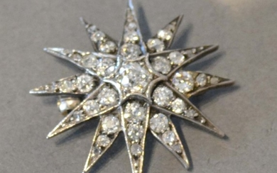 A White Gold Brooch in the form of a star with central diamo...