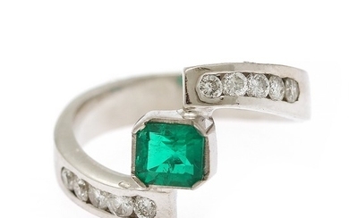 An emerald and diamond ring set with an emerald weighing app. 0.43 ct. flanked by ten diamonds, totalling app. 0.32 ct., mounted in 18k white gold. Size app. 50